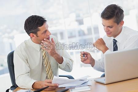 konzentrierende geschaeftsmaenner die im buero zusammenarbeiten