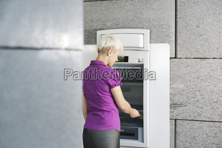 young woman withdrawing money with card