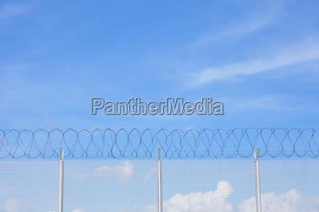 maschendrahtzaun mit stacheldraht unter blauem himmel