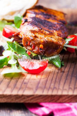 grilled pork steaks on a spit