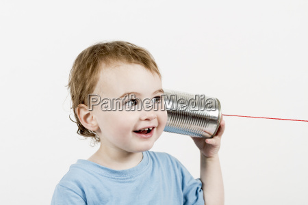 friendly child listening to tin can
