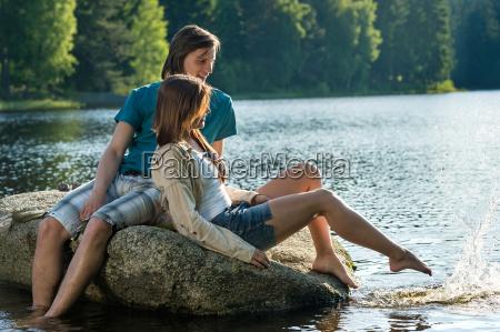 couple sitting on rock sharing romantic