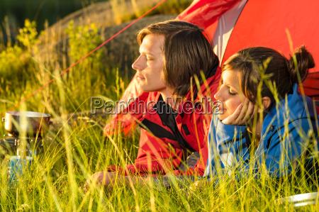 junges paar geniesst sonnenuntergang vom zelt