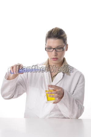 young chemist pouring liquids together