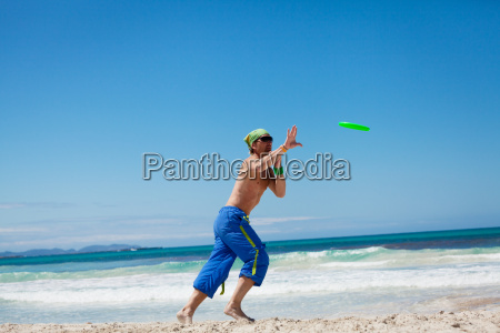 sporty man playing frisbee on the