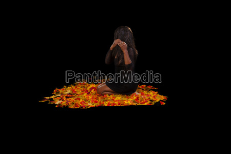 african american woman sitting autumn leaves