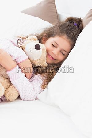 kleines maedchen schlafend mit teddybaeren