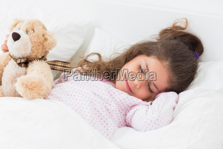 nettes maedchen schlaeft mit teddybaeren