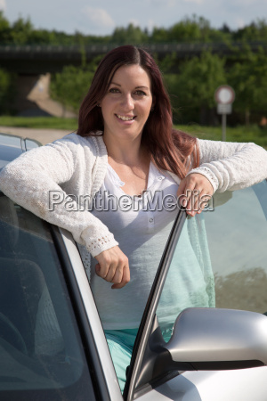 young woman leaning on a car