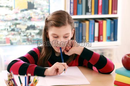 maedchen macht hausaufgaben am schreibtisch