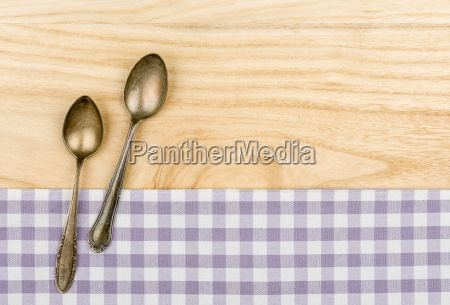 two silver spoons on a purple