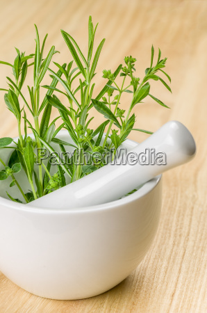 porcelain mortar with kitchen herbs