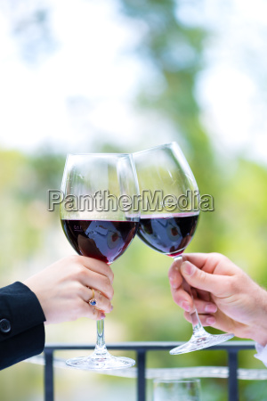 hands holding red wine glasses to