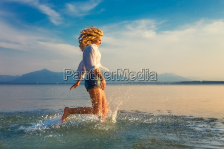 young blond woman running through water