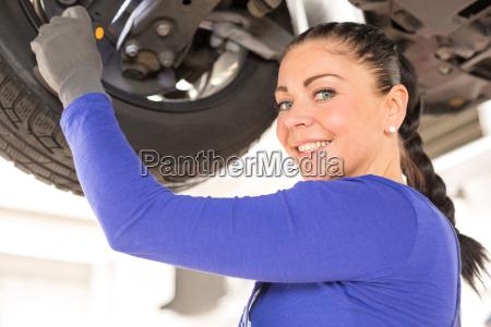 kfz mechanikerin repariert fahrzeug auf hebebuehne