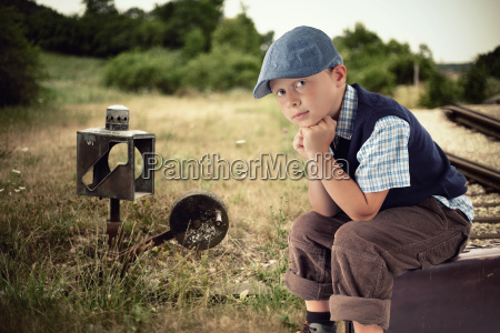 kleiner junge wartet am bahnhof