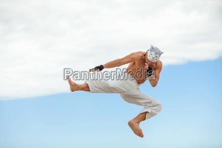 erwachsener sportlicher mann am strand springt