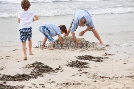 alleinerziehender vater mit soehnen kindern spielen