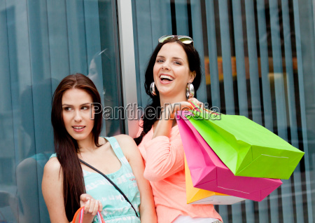 zwei junge lachende frauen beim shopping