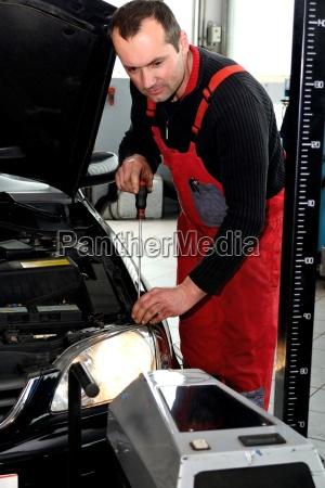 automechaniker stellt autobeleuchtung ein