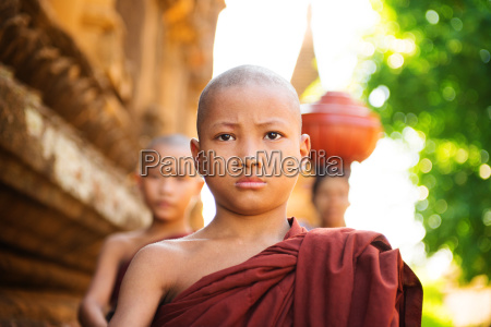 junge buddhistische moenche zu fuss am