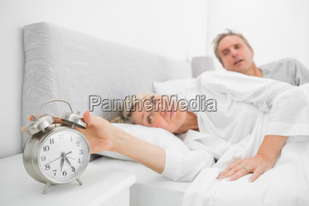 woman in bed with partner turning