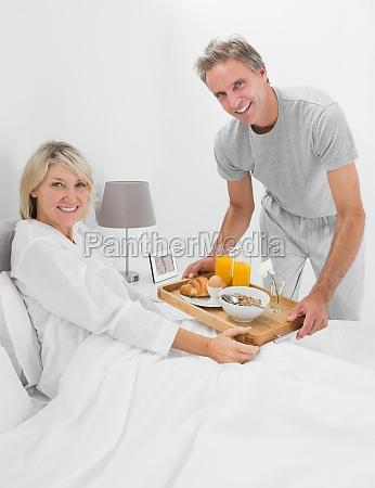 happy man giving breakfast in bed