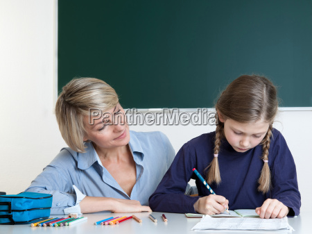 klassenlehrerin kontrolliert hausaufgaben