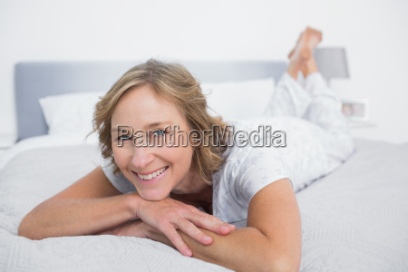 happy blonde woman lying on bed