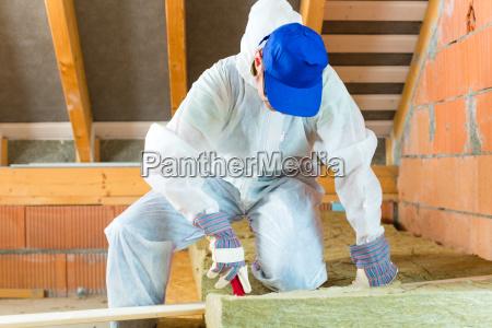 handwerker schneidet daemmmaterial