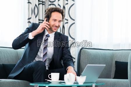 geschaeftsperson im hotel telefoniert mit einem