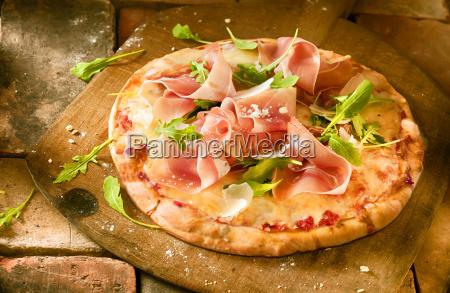 vorbereiten einer proscuitto und raketen pizza