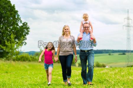 glueckliche familie laeuft in der wiese