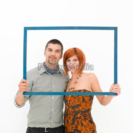 happy couple posing through a frame
