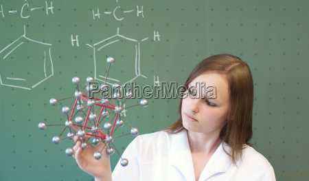 frau analysiert ein molekuelmodel im labor
