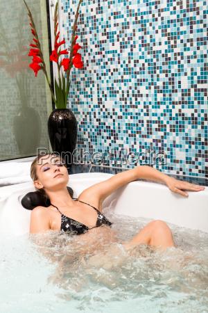 junge attraktive frau entspannt im whirlpool