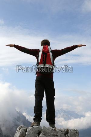 ein bergsteiger breitet die arme zum