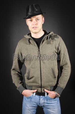junger mann in freizeitkleidung arme verschraenkt