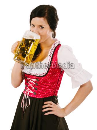 woman wearing dirndl and drinking oktoberfest