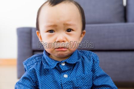 asiatisches baby fuehlt sich traurig an