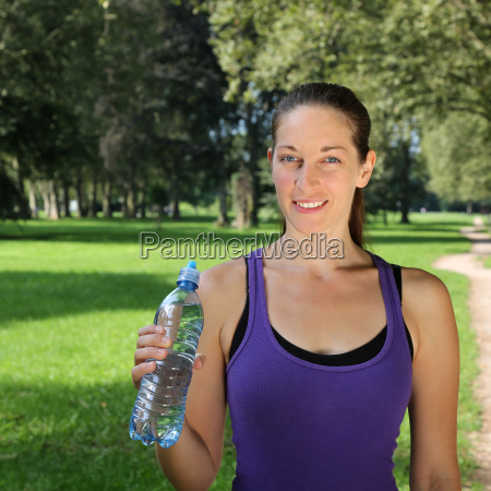 sporty woman with water bottle while