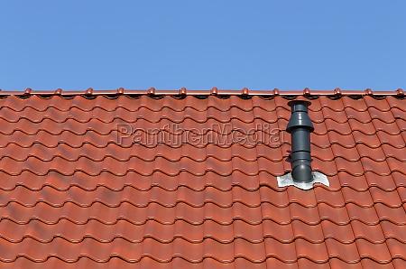 rotes dach mit schornstein vor blauem