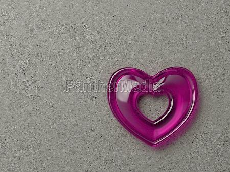 herz aus glas an steinwand pink