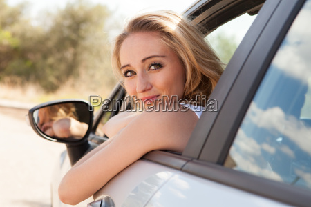 young laughing woman in car window