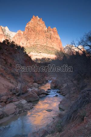 river flows sunrise glow rocky butte