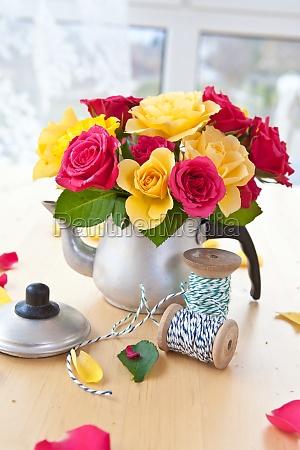 bunte rosen in kleiner kanne