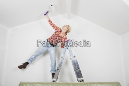 w43 woman painting gabled room renovation
