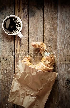 fresh flaky croissant with espresso coffee