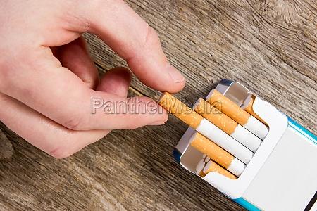 hand nimmt eine zigarette