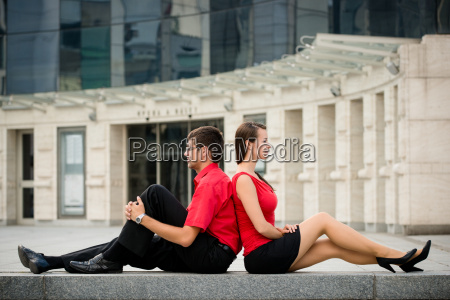 colleagues leant with backs outdoor